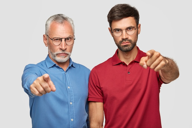 Scegliamo esattamente te! due uomini seri sicuri indicano con il dito indice, esprimono la loro scelta, indossano abiti luminosi, isolati sopra il muro bianco. uomo maggiore con figlio adulto al coperto