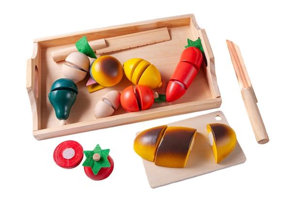 野菜をカットします。野菜と木で作られた2本のナイフを備えたトレイ教育玩具モンテッソーリ。白色の背景。閉じる。