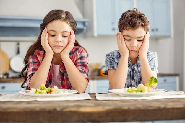 Мы ненавидим овощи. симпатичные несчастные темноволосые младшие брат и сестра сидят за столом, завтракают и грустно смотрят на овощи