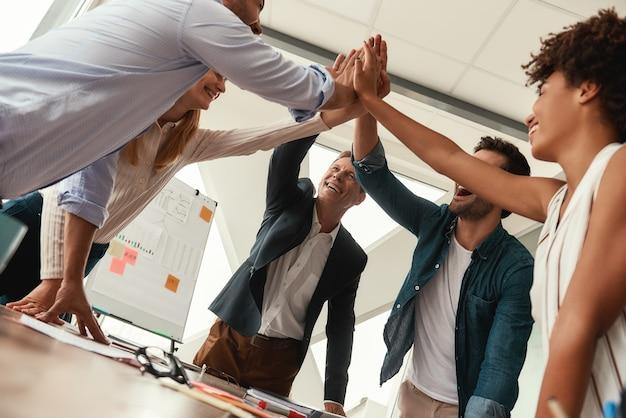 우리는 해냈습니다. 현대 사무실에서 함께 일하는 동안 비즈니스 사람들이 서로 하이파이브를 하고 웃고 있습니다. 팀워크. 성공