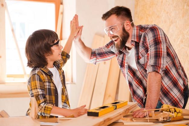 やりました!陽気な若い男性の大工と彼の息子は、ワークショップで働いている間、お互いにハイタッチを与えます