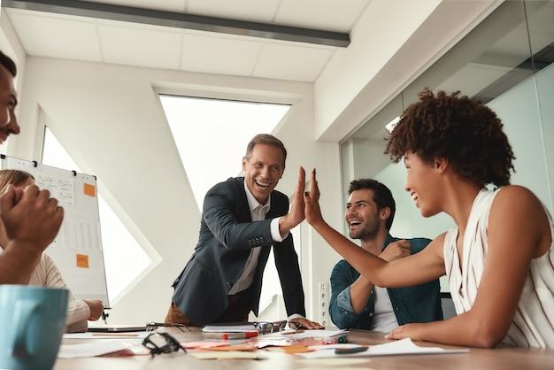 우리는 그것을 했습니다. 그의 동료에게 하이파이브를 주고 현대 사무실에서 회의를 하는 동안 웃고 있는 정장 차림의 행복한 성숙한 남자. 팀워크