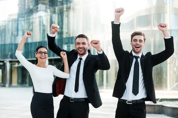 Мы сделали это! трое возбужденных молодых бизнесменов держат руки поднятыми и выражают позитив