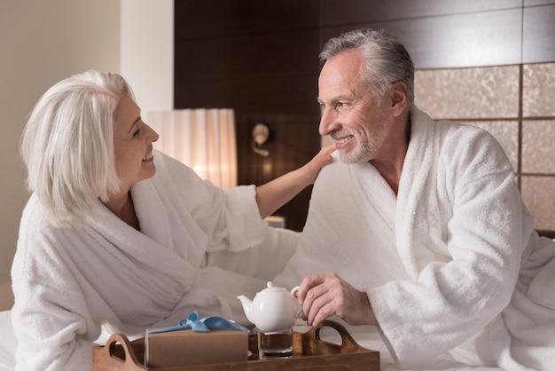 우리는 차를 마신다. 사랑과 관심을 표현하면서 침대에 누워 아침을 먹고 밝은 미소 세 커플