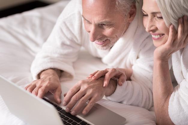 우리는 함께 자유 시간을 즐깁니다. 기쁨을 표현하면서 침대에 누워 노트북을보고 기쁘게 웃는 세 커플