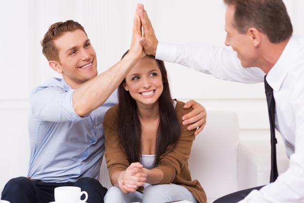 У нас есть сделка. счастливый молодой человек хлопает в ладоши с финансовым агентом, сидя вместе со своей женой