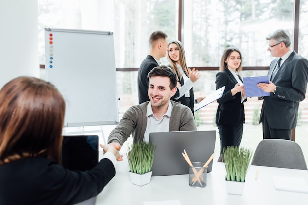 We have a deal! men shaking hands  woman and looking at each other with smile while sitting at the business meeting with their coworkers in modern office.