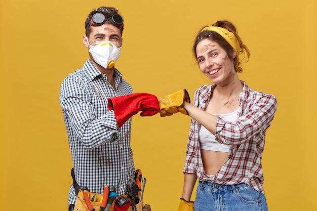やった!防護手袋とカジュアルな服を着た若い汚い保守作業員が、拳をまとめて作業を終えて喜んでいます。人、職業、チームワークの概念