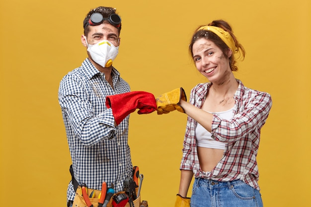 We have done it! young dirty maintenance workers wearing protective gloves and casual clothes keeping their fists together being glad to finish their work. people, profession, teamwork concept