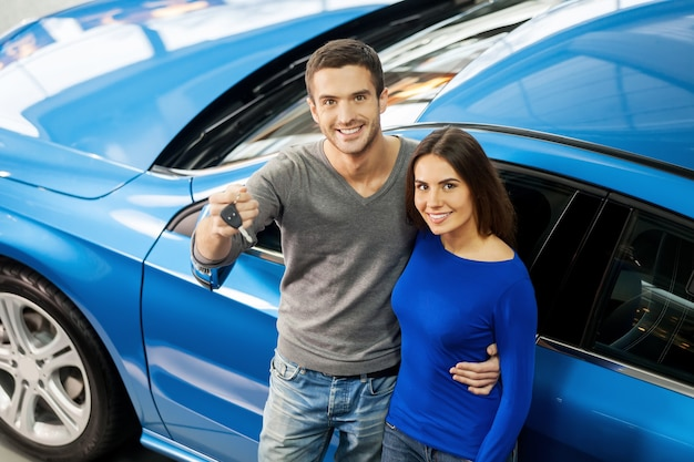 We have made the right choice. top view of young couple standing near the car at the dealership and holding a key