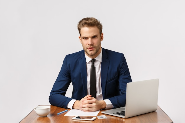 We have serious meeting here. focused smart successful businessman, lawyer sitting office lean on desk and looking strict at client as talking, have discussion, work with laptop and report