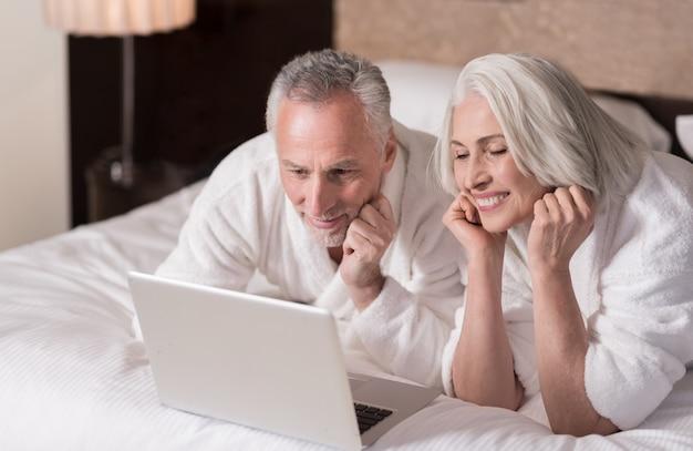 우리는 집에서 쉬고 있습니다. 관심을 표현하는 동안 침대에 누워 노트북을 찾고 기쁘게 웃는 세 커플
