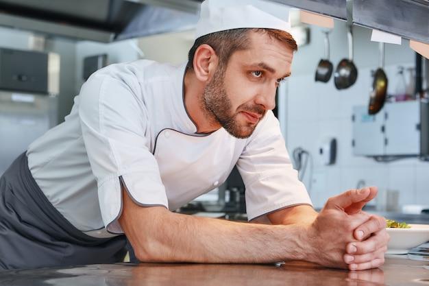 Мы знаем, что наш шеф-повар, мужчина, опирается на стол и смотрит в сторону, когда идет