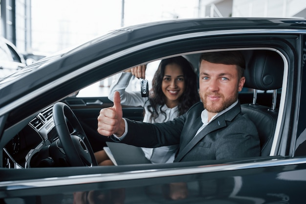 私たちはこれが好きです。自動車サロンで新しい車を試して素敵な成功したカップル
