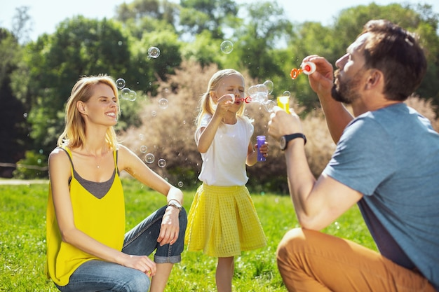 We love bubbles. content caring parents smiling and blowing soap bubbles with their little daughter
