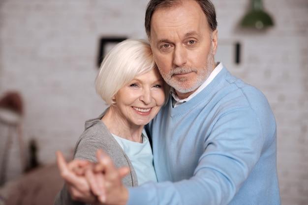 Мы любим. крупным планом портрет довольно улыбается пожилая женщина, стоя рядом с мужем и взявшись за руки.