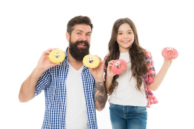 私たちはドーナツが大好きです。父の日プレゼント。甘い歯を持つお父さんに最適です。女児とお父さんは色とりどりの艶をかけられたドーナツを持っています。お菓子やお菓子のコンセプト。娘と父は甘いドーナツを食べます。甘いデザート。