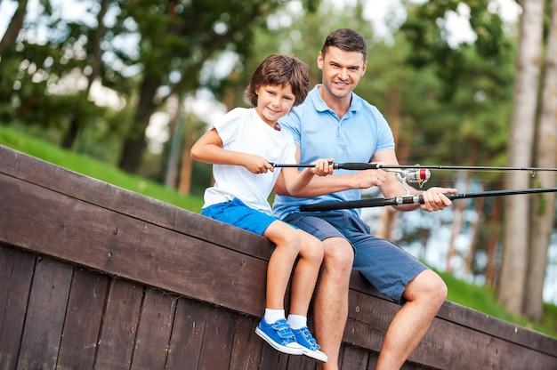 Мы любим рыбачить вместе. веселый отец и сын вместе ловят рыбу и улыбаются, сидя на набережной