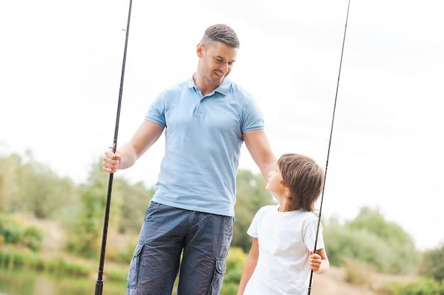 Мы любим рыбачить вместе. веселый отец и сын держат удочки и с улыбкой смотрят друг на друга, стоя на берегу реки вместе