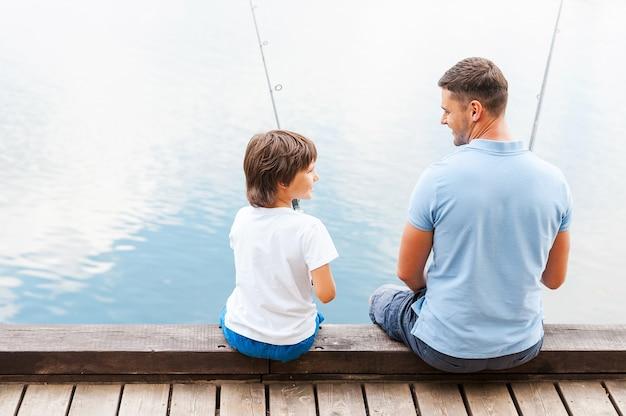 Мы любим рыбачить вместе. вид сзади отца и сына, ловящего рыбу, сидя на набережной вместе