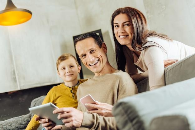 우리는 가제트를 좋아합니다. 소파에 앉아 카메라에 밝게 미소 짓고 가제트와 함께 포즈를 취하는 즐거운 경쾌한 젊은 가족 프리미엄 사진