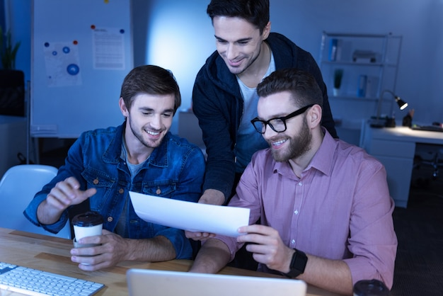 We love our job. happy delighted handsome programmers looking at the sheet of paper and smiling while enjoying their work