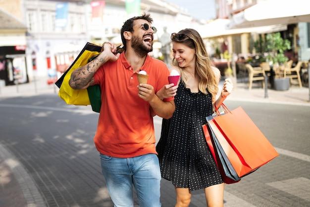 私たちは一緒に買い物をするのが大好きです。ショッピングや旅行中に通りを歩いている美しい若い愛情のあるカップル