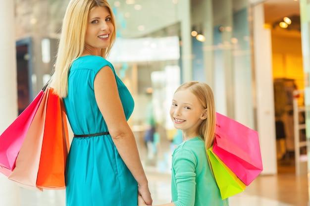 우리는 함께 쇼핑하는 것을 좋아합니다! 쾌활한 금발 머리 엄마와 딸 쇼핑백을 들고 쇼핑몰에 서있는 동안 어깨 너머로보고
