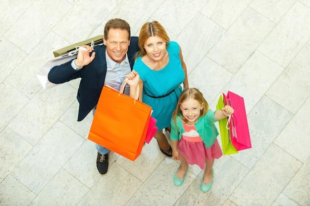 우리는 쇼핑을 좋아합니다! 쇼핑몰에 서 있는 동안 쇼핑백을 들고 카메라를 보며 웃는 쾌활한 가족의 상위 뷰