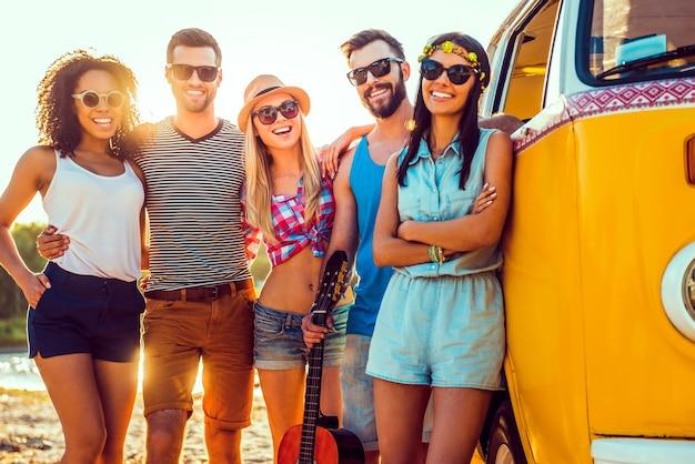 Мы любим проводить время вместе. группа улыбающихся молодых людей, связанных друг с другом и смотрящих в камеру, стоя возле своего минивэна
