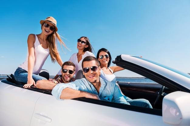 私たちは一緒に時間を過ごすのが大好きです!彼らの白いコンバーチブルでロードトリップを楽しんで、カメラに笑みを浮かべて若い幸せな人々のグループ