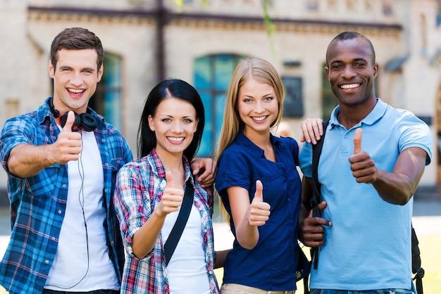 私たちは勉強が大好きです!屋外でお互いに近くに立っている間、親指を立てて笑っている4人の幸せな若者