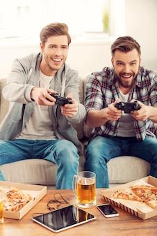 私たちはこのゲームが大好きです!ソファに座ってビデオゲームをプレイする2人の陽気な若い男性