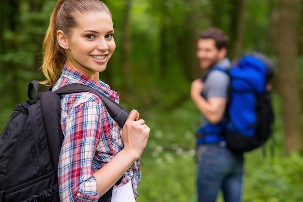 우리는 여행을 좋아합니다. 배낭을 메고 어깨 너머로 보고 웃고 있는 아름다운 젊은 여성