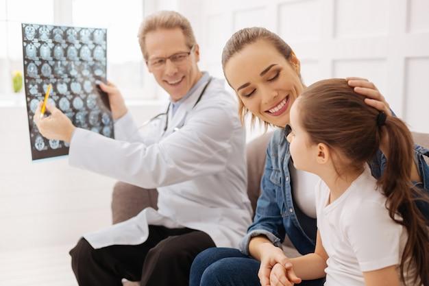 やった。医者が子供がついに健康になったと言って喜んでいる陽気でかわいい興奮した母と娘