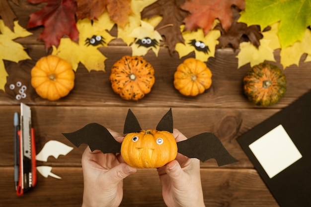 We make gifts for halloween. making a funny bat out of a small yellow pumpkin. halloween party decor. diy instruction. step by step guide.