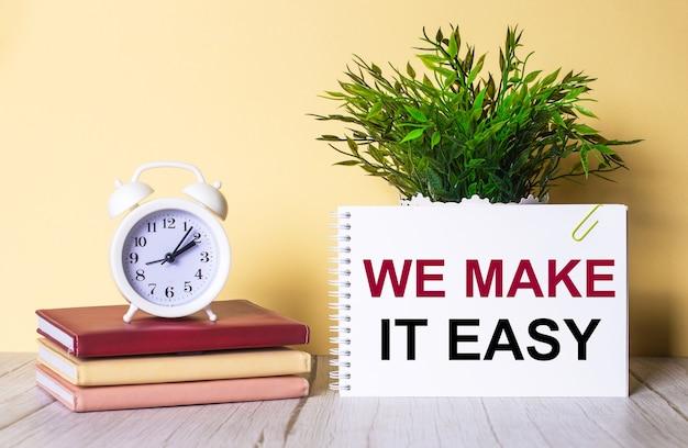 «мы делаем это легко» написано в блокноте рядом с зеленым растением и белым будильником, который стоит на красочных дневниках.