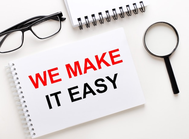 We make it easy is written in a white notebook on a light background near the notebook, black-framed glasses and a magnifying glass