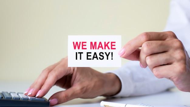 私たちはそれを簡単にします、ライトオフィスの職場で女性が電卓キーを押すことによって示される名刺のメッセージ、選択的な焦点、ビジネスと財務の概念