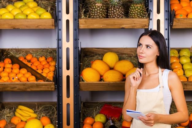 もっとオレンジが必要です。さまざまな果物を背景に食料品店に立っている間、メモ帳を持って目をそらしているエプロンの思いやりのある若い女性