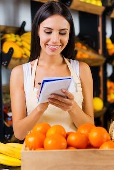 Нам нужно больше мандаринов. красивая молодая женщина в фартуке, делая заметки в блокноте и улыбаясь, стоя в продуктовом магазине с разнообразными фруктами на заднем плане