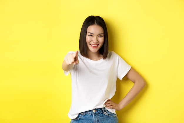 Мы нуждаемся в вас. уверенная азиатская женщина улыбается, указывая пальцем на камеру, приглашает присоединиться к ней, манит или выбирает кого-то, стоя на желтом фоне.