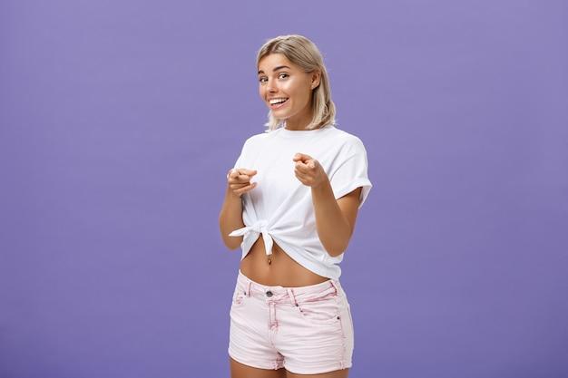 Вы нужны нам в команде. радостная дружелюбная и красивая белокурая студентка в белой футболке и шортах, указывающая вперед