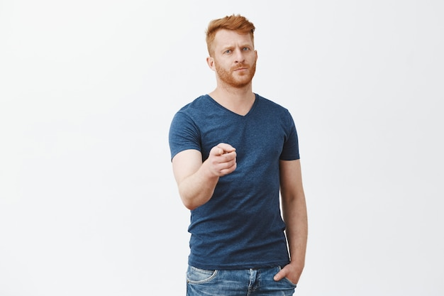 We need you, join us. serious-looking handsome and confident mature bearded redhead male in casual blue t-shirt, pointing with index finger staring seriously and strict over grey wall