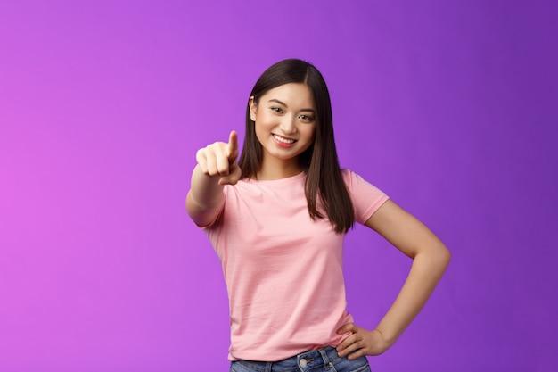 私たちはあなたに私たちのチームが必要です。フレンドリーでかっこいい発信アジアの女性ブルネットポインティングカメラ、人差し指を示し、やる気のある笑顔、人を選ぶ、決定を下す、紫色の背景に立つ。