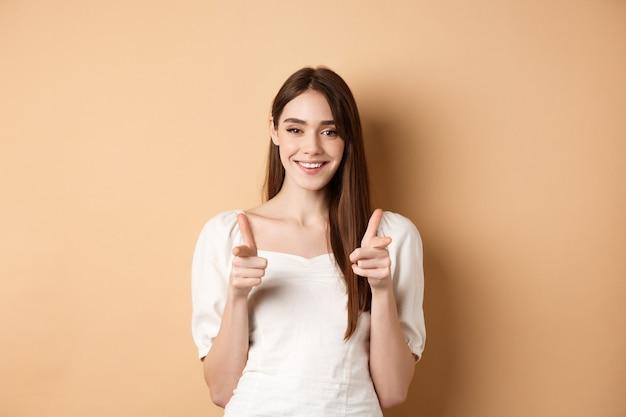 우리는 당신이 필요합니다. 베이지 색 배경에 서서 손짓하거나 사람들을 초대하기 위해 카메라에서 손가락을 가리키는 젊은 여자를 웃고.