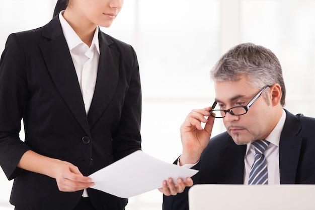 Здесь нам нужна ваша подпись. уверенный зрелый бизнесмен сидит за столом и поправляет очки, в то время как молодая женщина в строгой одежде показывает документ