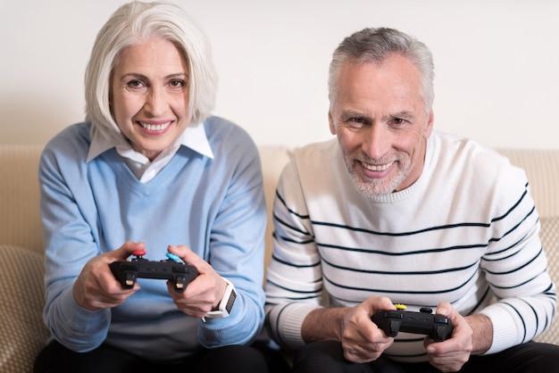 私たちはゲームをします。ソファに座って喜びを表現しながらゲーム機を持って喜んで笑顔の老夫婦