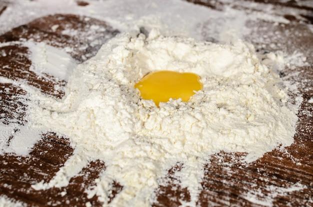 Готовим тесто на деревянном столе.
