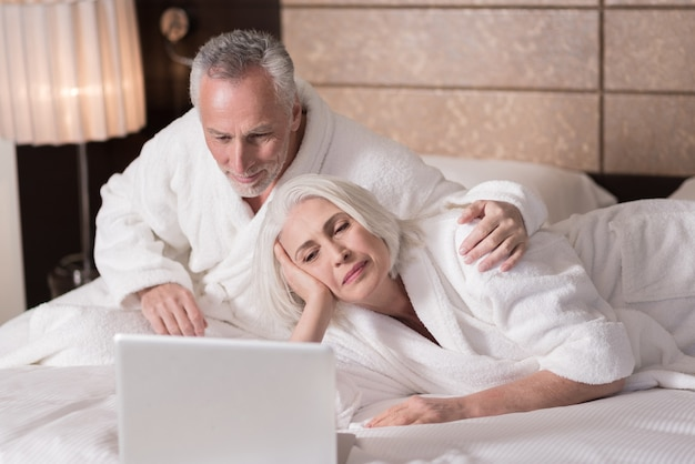우리는 휴식을 취합니다. 쾌활한 미소 세 커플 침대에 누워 관심을 표현하는 동안 노트북을 찾고